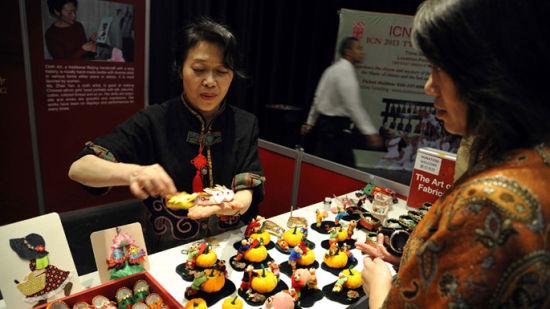 赵艳女士向参观者展示传统布艺制作的手工艺品。