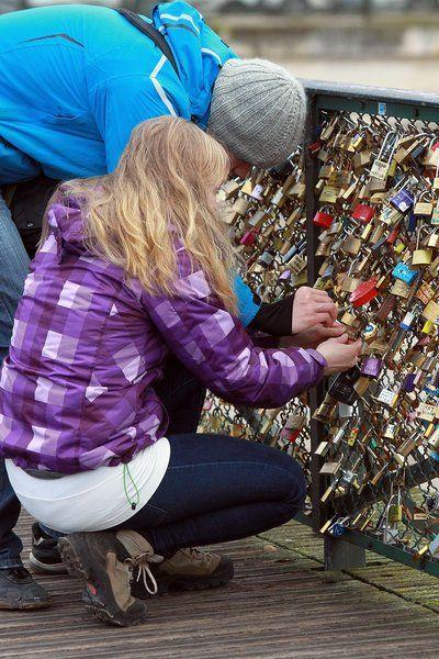 造访的人们在桥上锁上写着爱人姓名首字母或者写着爱语的锁,并将钥匙扔入河水之中。