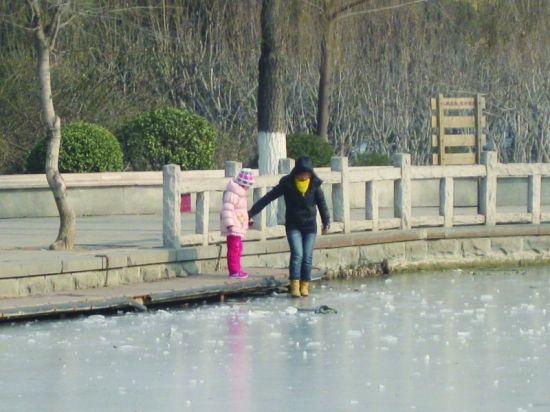市民带孩子在湖面玩耍