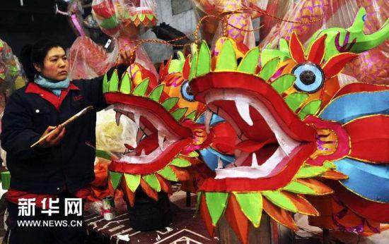 淄博市周村区和平社区传统花灯厂工人给花灯做最后的修饰。