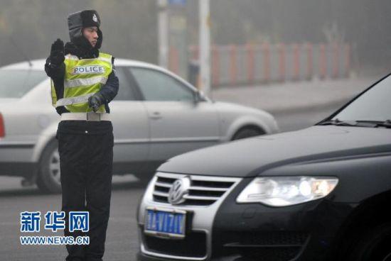 济南交警在雾霾中指挥交通。