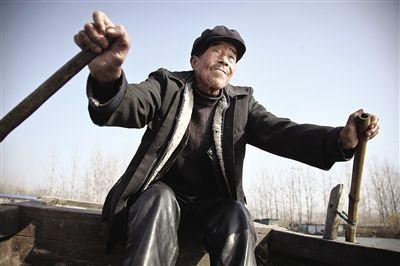 微山湖上,老人划着船去往湖心的大捐村。