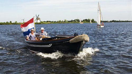 一对夫妇正航行在荷兰的Kaag湖面上,赛船在夏季很常见。