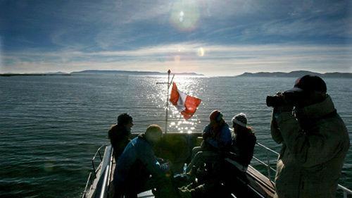 游客们在船上交谈、拍照,观赏秘鲁境内的的的喀喀湖。