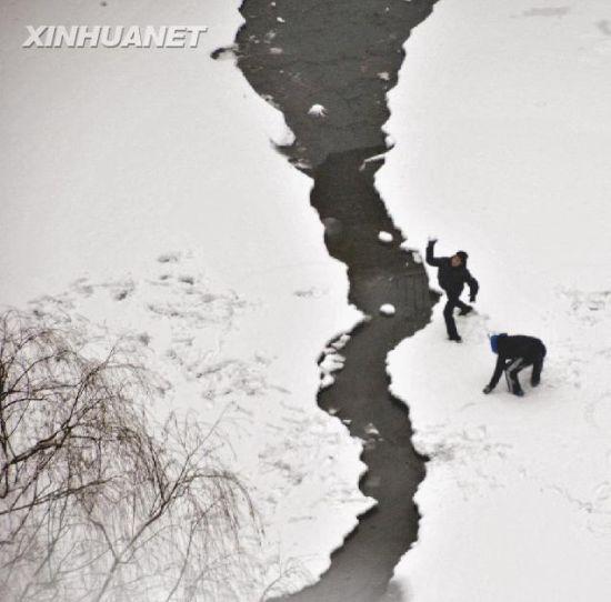两名儿童在济南被冰雪覆盖的兴济河河床上嬉戏。