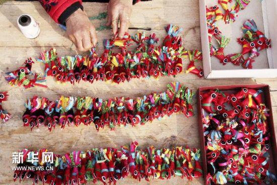 """1月27日,山东省临沂市郯城县郯城街道后东二村的蒋纪霞老人在整理自己缝制的""""春鸡"""",准备到年集上售卖。(张春雷 摄)"""