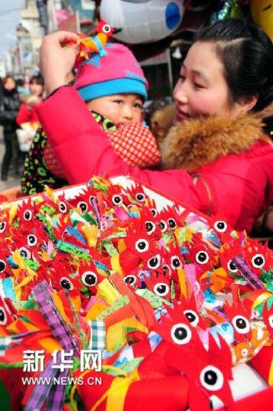 """1月27日,一位女士在山东省临沂市郯城县马头镇集市上为孩子选购""""春鸡""""。(房德华 摄)"""