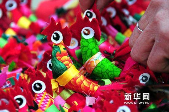 """1月27日,在山东省临沂市郯城县马头镇集市上,一名民间艺人展示自己缝制的""""春鸡""""。(房德华 摄)"""