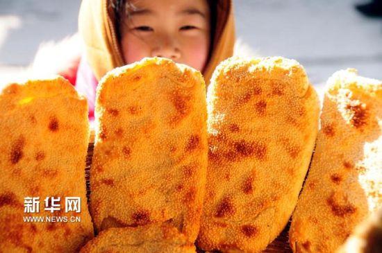 """2月2日,在临沂市郯城县马头镇一老字号食品店,一名小女孩被刚出炉的""""朝牌""""所吸引。(房德华 摄)"""