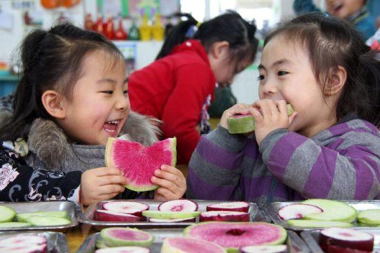 """2月4日,在山东南部的枣庄市,枣庄实验幼儿园的小朋友在吃生萝卜""""咬春""""。"""
