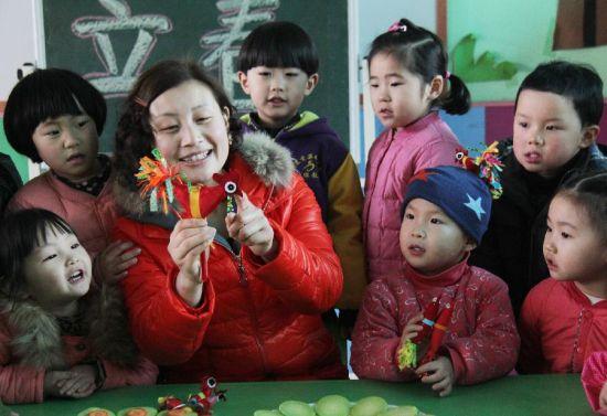 """2月4日,山东省临沂市郯城县一所幼儿园的老师在为小朋友介绍""""春鸡""""有关的民俗。"""