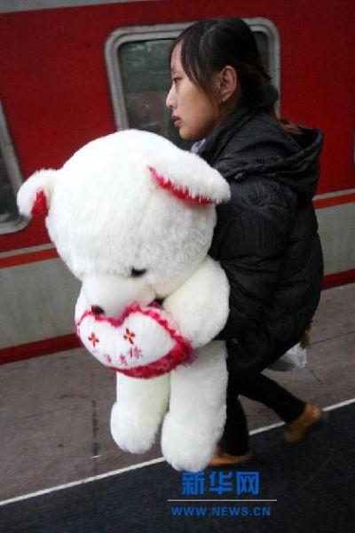 """2月3日,在山东烟台火车站,一名女孩抱着印有""""一生有你""""的毛绒玩具上车。"""