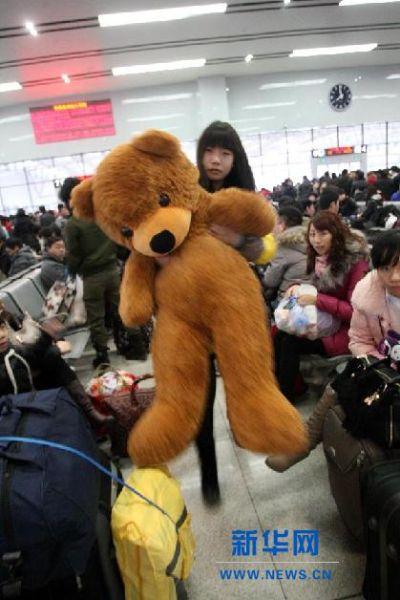 2月3日,在山东烟台火车站,一名女孩抱着毛绒玩具候车。