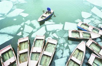 工作人员在映日湖面上破冰