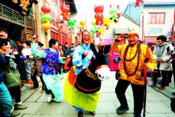 """2月10日,一名外国留学生在淄博周村古商城体验中国民俗活动""""跑驴""""。"""