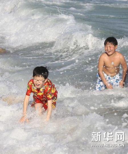 """2月11日,小朋友在海南省三亚市海边游玩,欢度""""旅游年""""。 (陈文武 摄)"""