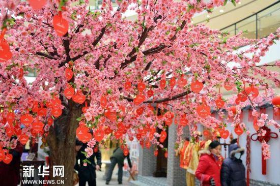 济南一家商场用挂满祝愿卡的花饰烘托节日气氛(2月13日摄)。新华社记者 朱峥摄