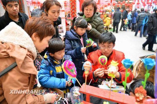 2月13日,市民在一家商场里了解、购买年俗工艺品。新华社记者 朱峥摄