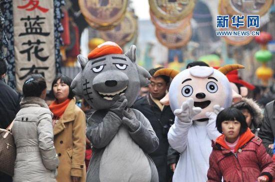 """2月11日,大年初二,""""喜羊羊""""(右)与""""灰太狼""""在山东淄博周村古城内陪伴游人。(董乃德 摄)"""