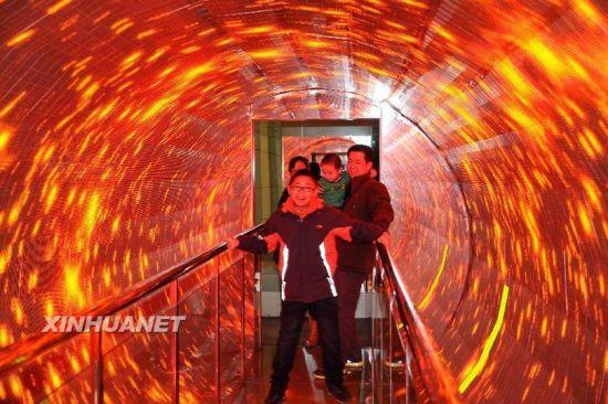 """2月15日,一名济南市小学生在山东省科技馆体验""""旋转走廊""""。参观者受视觉参照物旋转的影响,实际平直的路变得十分难走。新华社记者 徐速绘摄"""