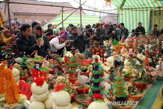 2月16日,在山东省菏泽市曹县桃源集镇,村民在观看花供作品。