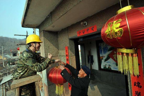 2月23日,国家电网山东淄博供电公司农电工苏明法(左)为88岁老人李治得家挂上大红灯笼。