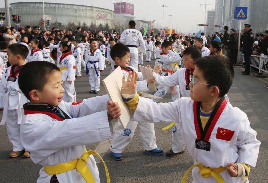 2月23日,在山东青岛,一群小朋友在街头进行跆拳道表演。