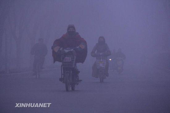 """2月25日,在山东省聊城市街头,市民""""全副武装""""在大雾中出行。"""