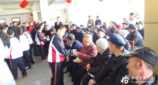 孩子将捐赠的物品送到每一位老人的手里