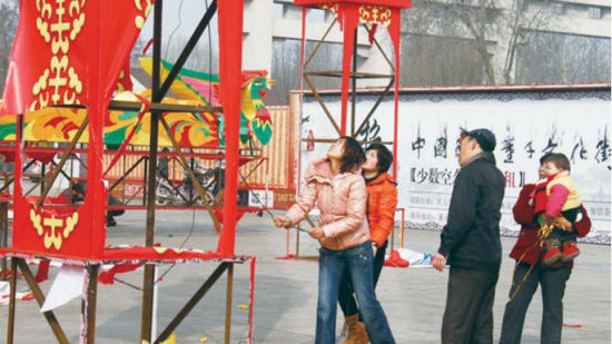 """26日,元宵节过后第二天,董子文化街内有工作人员忙着拆卸花灯,一时间花灯的组成部分灯泡、绢、电线成了市民手中的""""抢手货""""。本报见习记者 王小会 摄"""