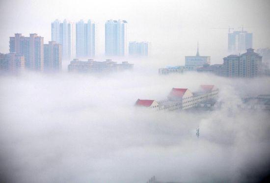 2月27日,山东威海海滨中路的部分建筑在平流雾中若隐若现。