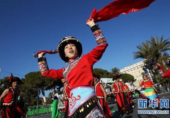 """3月2日,在法国南部海滨城市尼斯,来自贵州省六盘水钟山区歌舞团的演员在狂欢节游行上表演""""彝族铃铛舞""""。"""