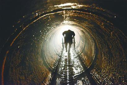 进入坑道以后,工人就得弓着腰推车。