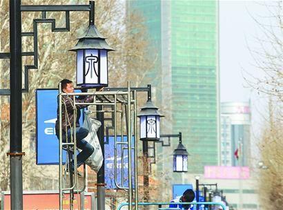 """工人正在山东省济南市泉城路安装印有""""泉""""元素的路灯"""