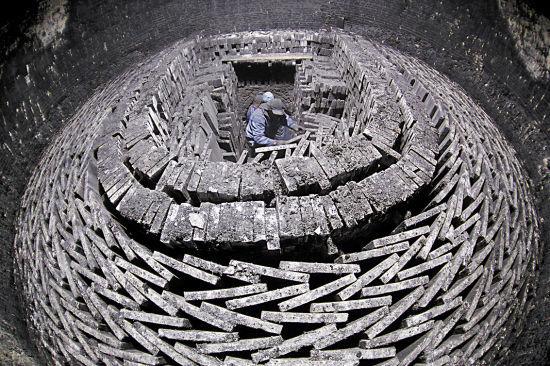 """已经充分冷却的柴窑内,五千多块""""金砖""""按尺寸整齐地分类,码放成同心圆状。砖雕用的""""金砖""""完全按照古法工艺烧制"""