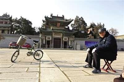一位老人在山陕会馆门前广场上晒太阳。