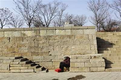 崇武驿大码头,一位老人在背风向阳处缝衣服。