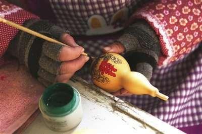 堂邑镇路庄村,正在加工制作的烙画葫芦。