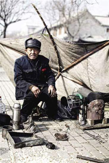 聊城市东昌府古城内,用传统工具加工爆米花的老人。