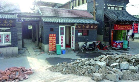 鞭指巷北口堆放着拆下来的石块 记者曹建民实习生王亚男摄