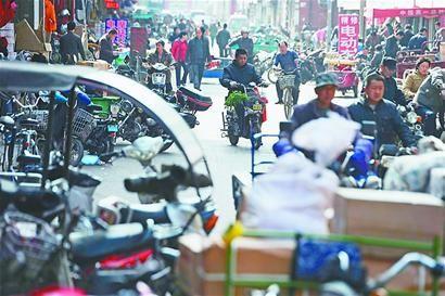 交通厅街两侧的商家将摩托车和配件摆在店门前的道路上 实习生倪玉星 摄