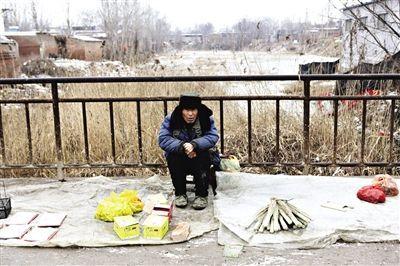 阿城镇古运河小桥上,一位摆地摊的老人。