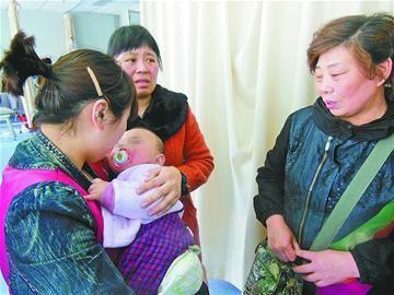 馨馨在妈妈的怀抱里逐渐安静下来 记者孙钰 摄□本报记者 孙钰