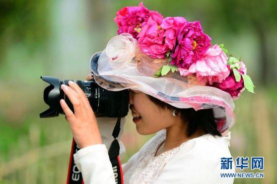 4月16日,在菏泽市曹州牡丹园,一位游客头戴牡丹花环拍照。新华社记者郭绪雷 摄.jpg