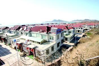 """以前以打渔为主的黑石嘴渔村现在已经变成建筑风格统一规范的""""渔家乐""""村庄。 (赵金阳 摄)"""