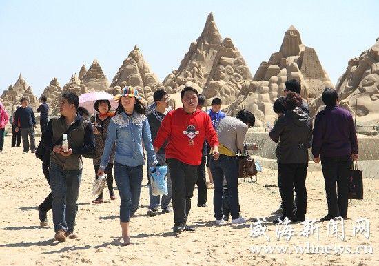昨日,游客在南海新区大型沙雕前漫步。 记者 张虎林 摄