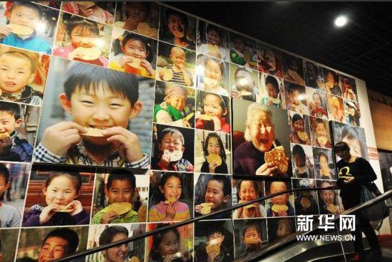 游客从周村古城景区内一家烧饼博物馆的海报前走过。.jpg