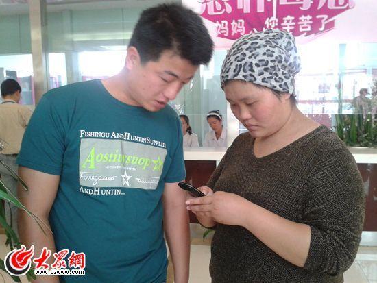 21岁的李凤云和丈夫在翻看儿子照片