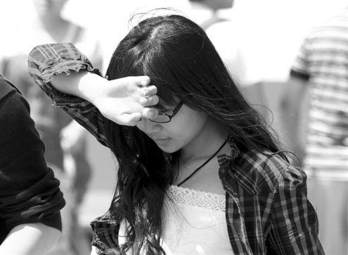 昨日(13日),出行的市民用手臂遮挡烈日。当日,省城最高温达到33.5℃