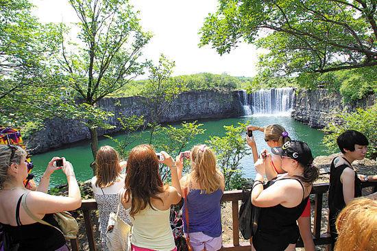 俄罗斯游客在镜泊湖拍摄吊水楼瀑布 图/张燕辉